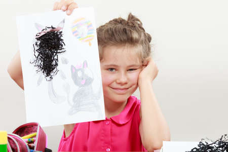 elementary age: Little girl draw in the classroom. Being creative in elementary age