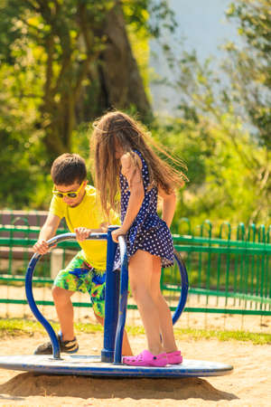actively: Joyful active childhood. Playful kids playing on playground. Children having fun in summer. Young tourists spending actively time. Stock Photo