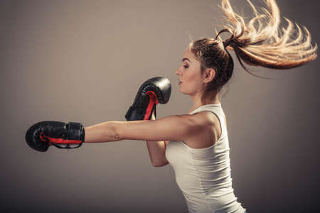 opponent: Energy fighting boxing with opponent. Sports and bodybuilding. Strong young woman punch enemy. Girl with ponytail wear white tank top and boxing gloves side view.