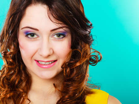 silky hair: Closeup smiling woman face, girl with long brown curly hair colorful makeup portrait on green Stock Photo