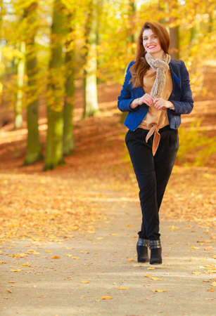 Fashionable young woman in forest. Girl taking walk through the park. Nature relax fashion concept. Stock Photo