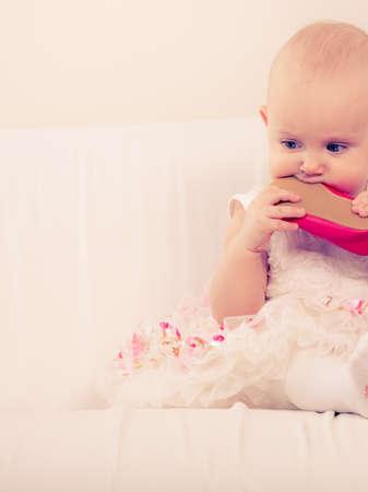 poco: Infantil en el tiempo de la dentición. linda niña dulce morder mascar zapato rojo. adorable niño joven con vestido de princesa blanca. Foto de archivo