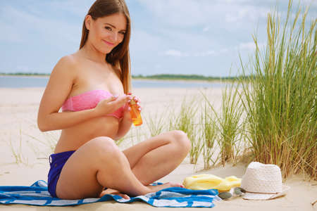 sun oil: Skin protection in summer. Woman on beach using sun oil. Young beauty girl taking sunbath on sunny day. Holidays time.