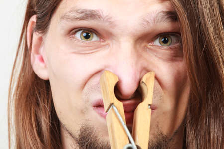 long nose: Man with clothespin clip peg on his nose. Young long haired guy feeling unpleasant odor stink. Bad smell concept.