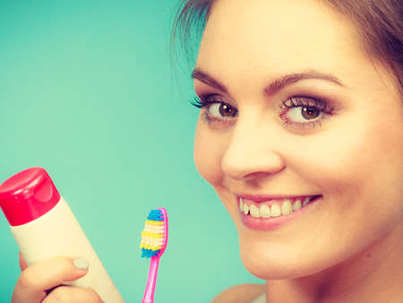 Woman holding brush and tooth paste for teeth cleaning. Happy smiling girl with toothbrush. Oral hygiene. Studio shot green background Stock Photo