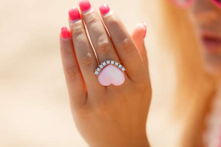 propose: Beautiful heart ring on hand with diamonds. Propose in suny day outside. Love concept.