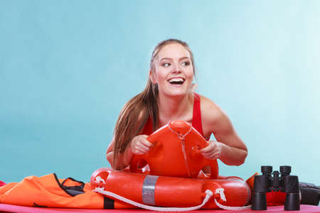 Happy lifeguard lying on rescue tube buoy and ring lifebuoy. Joyful woman girl having fun. Accident prevention and rescue.