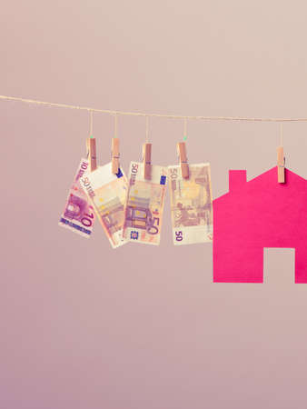 business savings: Red house with green key and banknotes cash hang on laundry line. Selling and buying home concept.