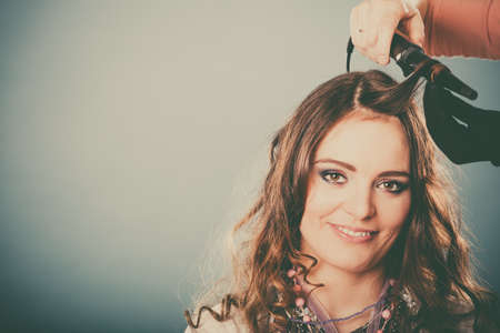 curler: Hairdresser curling woman hair with electric iron curler tong. Hairstylist making girl hairstyle. Attractive pretty young female. Beauty. Instagram filter.