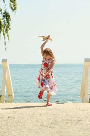 Little girl child kid having fun with cardboard paper plane airplane at beach.