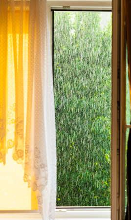 windowpane: Summer rainy outside window, water drops droplets raindrops on glass windowpane. Downpour rain.