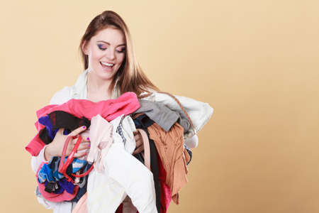 tidying: Happy young woman carrying stack pile of dirty laundry clothes. Girl cleaning tidying in studio. Stock Photo