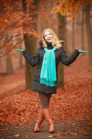 autumn young: Autumn time concept, leisure. Girl is walking through the park. Young woman speanding free time outside, enjoying good autumnal weather.