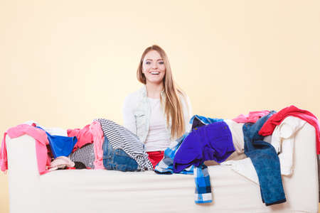 messy clothes: Happy woman sitting on sofa couch in messy living room. Young girl surrounded by many stack of clothes. Disorder and mess at home.
