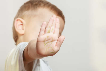express feelings: Express negative emotions. Childhood and feelings. Little boy show hand outstretched arm with stop gesture. Hold hand in air.