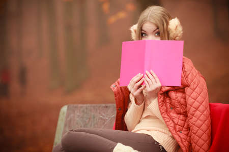 Outdoor nature season relax leisure concept. Young lady with literature. Blonde girl covering her face by red book sitting on bench in autumnal woodland.