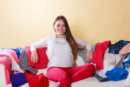 living things: Happy woman sitting on sofa couch in messy living room. Young girl surrounded by many stack of clothes. Disorder and mess at home.