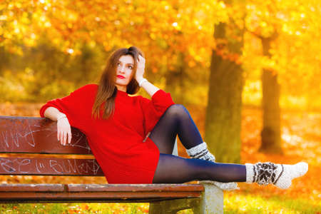Fall lifestyle concept, harmony freedom. Thoughtful pensive woman fashion girl in warm wool socks relaxing sitting on bench in autumnal park, outdoor Stock Photo