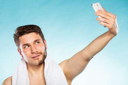 Young man with half shaved face beard hair taking selfie self photo with smartphone camera. Handsome guy on blue. Skin care and hygiene.