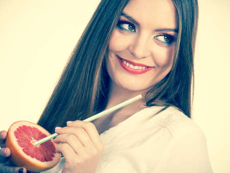 Woman attractive long hair girl eyes makeup holding grapefruit citrus sipping juice from fruit. Healthy diet food. Summer vacation holidays concept. Toned image Stock Photo