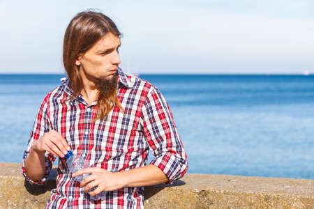 man long hair: Man long hair wearing plaid shirt relaxing by seaside drinking water at summer sunny day