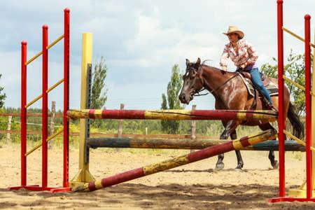 salto de valla: Activo caballo vaquera montar entrenamiento de la mujer occidental que salta sobre la cerca. competición deporte ecuestre y actividad. Foto de archivo