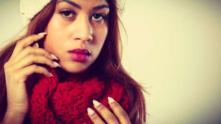 mulatto: Fashion, snowy time people concept. Woman with red winter clothing. Mulatto model wearing warm cap and scarf
