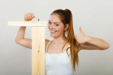 enthusiast: Successful soman assembling wooden furniture using hex key. DIY enthusiast. Young girl with thumb up doing home improvement.