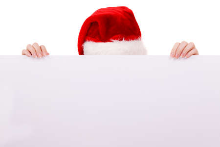 over the edge: Woman holding banner sign peeking over edge of blank empty billboard with copy space for text. Girl in santa claus hat having fun. Christmas advertisement copyspace. Stock Photo