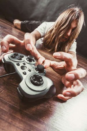 dependency: Addiction and dependency concept. Young man with pad joystick playing games