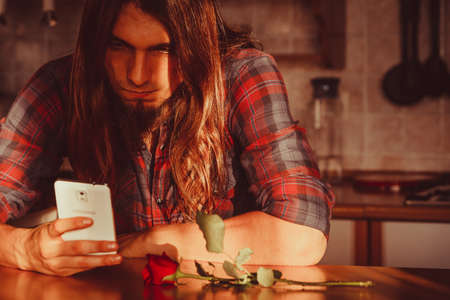 decepción: Disappointment and depression. Unrequited love concept. Young worried disappointed man with single red rose and smartphone mobile phone waiting for his girlfriend.