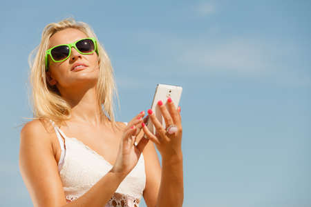updated: Young girl with sunglasses using her mobile phone to be updated. Active relax. Social network and internet concept.