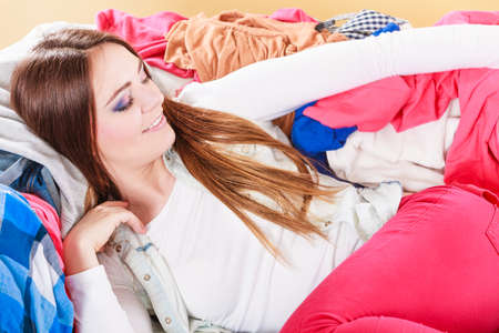 glad: Portrait of happy glad young woman girl lying on stack of clothes. Disorder and mess.