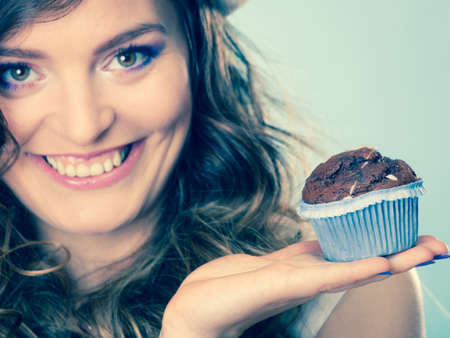 indulging: Sweet food sugar make us happy. Smiling woman curly hair holds cake chocolate muffin in hand