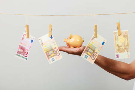 laundry line: Spending money concept. Male hand with piggybank and euro banknote cash hang on laundry line. Savings.