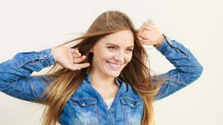 coiffure: Young girl with waving hairs. Cheering woman standing in wind. Fashion coiffure leisure lifestyle concept.