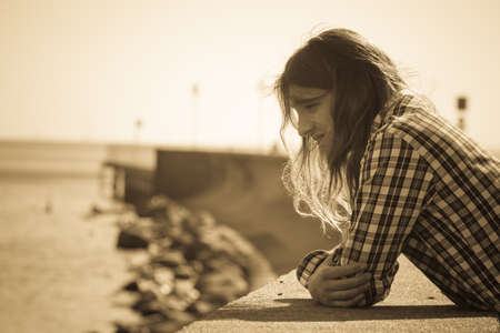 long depression: Man long hair alone on sea shore, lost in thought, is concerned sad and stressed about events in his life. Unemployment depression concept Stock Photo
