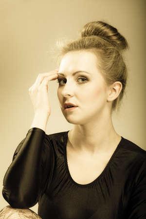 Portrait of young beautiful girl blonde woman makeup and hair bun vintage aged tone Foto de archivo - 126096849