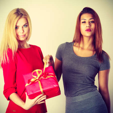 suprise: Gifts giving for any occasion. Two young ladies with red gift. Blond girl has nice dress and mulatto lady wears grey outfit. Both are very beautiful.