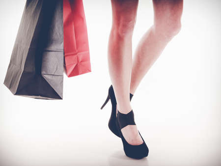 Stylish young woman love shop. Long legs in black high heels. Girl in short red dress hold shopping red and black bags.