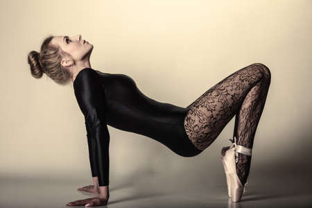 Graceful beautiful woman ballet dancer full length studio shot  gray background Stock Photo