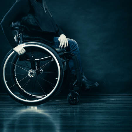 handicap people: Real people, disability and handicap concept. Young woman invalid girl sitting on wheelchair part of body studio shot on black