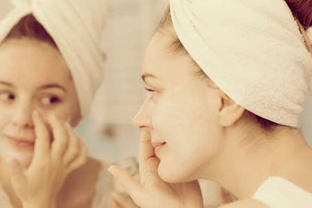 complexion: Woman applying mask moisturizing skin cream on face looking in bathroom mirror. Girl taking care of her complexion layering moisturizer. Skincare spa treatment.