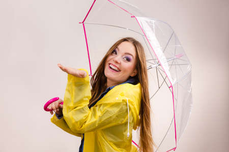 Woman rainy girl in waterproof yellow coat standing with transparent umbrella stretching arm, holds out her palm to catch rain falling water. Forecasting weather season concept Stock Photo