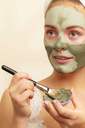 complexion: Skin care. Woman applying with brush clay mud mask to her face. Girl taking care of oily complexion. Beauty treatment.
