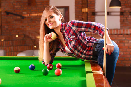 Fashion and fun concept. Young charming girl posing by billiard pool. Attractive fashionable woman casual style spending time on recreation.