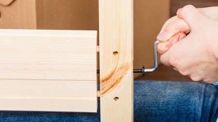 enthusiast: Human hand assembling wood furniture using hex key. DIY enthusiast. Home improvement.