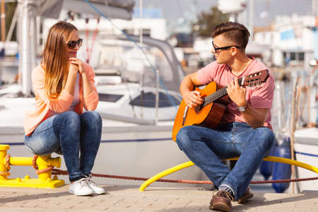 charmed: Love romance affection music sound talent concept. Girl charmed by musican. Young guitarist playing on instrument in port.