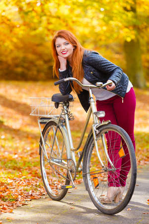 ginger hair: Nature, outdoors concept. Ginger hair girl with her bike in the park. Golden autumn brings beautiful weather. Stock Photo