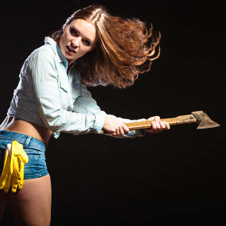 feminist: Sexy seductive woman holding axe chopper. Strong girl feminist working in man profession. Independent female.